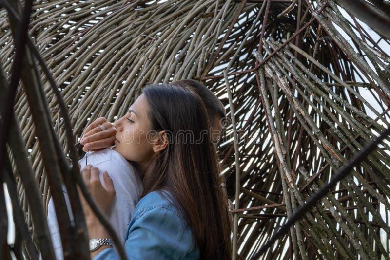 Jeunes couples étreignant l'extérieur au fond en bois à la campagne photos stock