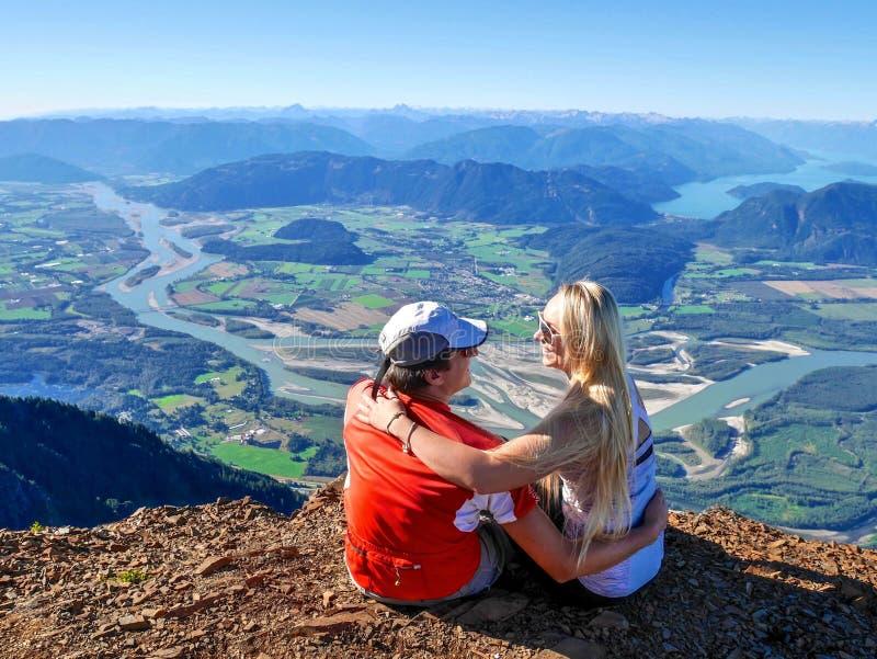 Jeunes couples étreignant sur la falaise avec une belle vue image libre de droits