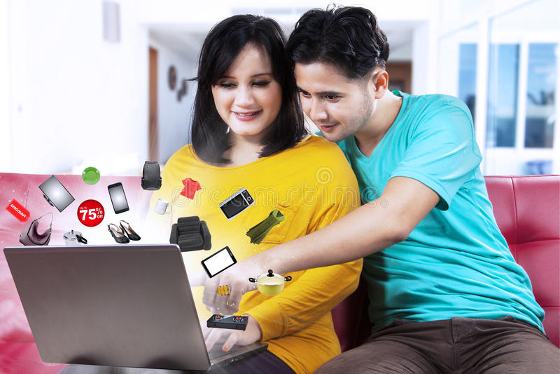 Jeunes couples achetant en ligne avec la remise images libres de droits