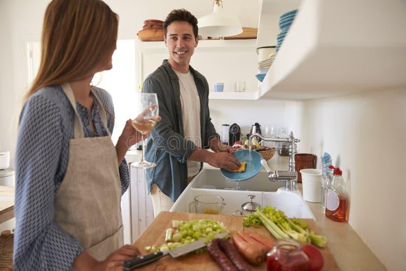 Jeunes couples adultes préparant la nourriture, regardant l'un l'autre photos libres de droits