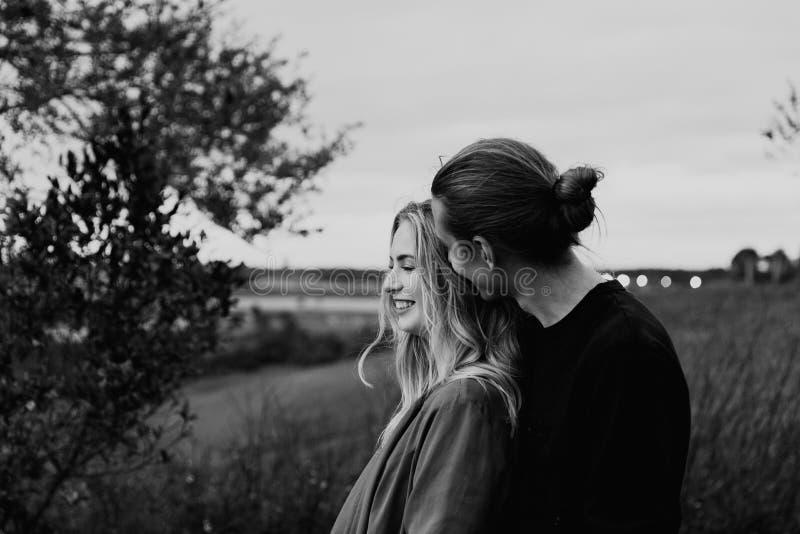 Jeunes couples adultes romantiques et affectueux au parc regardant la nature et l'horizon pour des images de portrait photo libre de droits