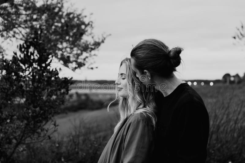 Jeunes couples adultes romantiques et affectueux au parc regardant la nature et l'horizon pour des images de portrait image stock