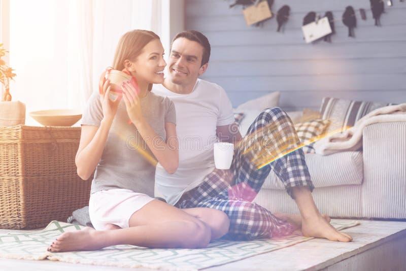 Jeunes couples affectueux étant à la maison photographie stock