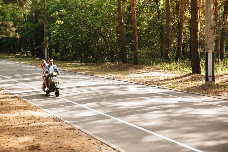 Jeunes couples affectueux attrayants sur le scooter dehors Regard de côté photo libre de droits