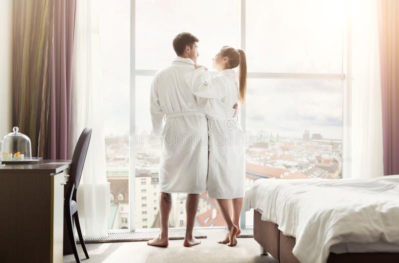 Jeunes couples affectueux dans la chambre d'hôtel pendant le matin image stock