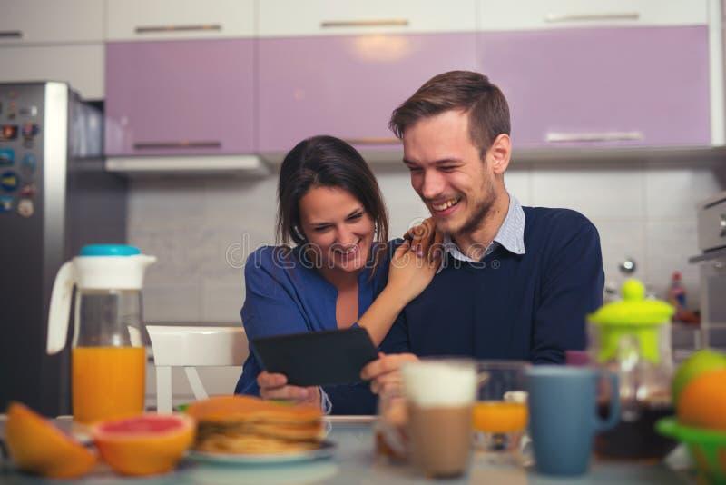 Jeunes couples affectueux dans la cuisine par la table de petit déjeuner dans MOR image stock