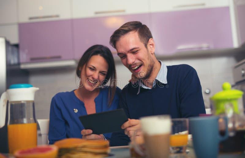 Jeunes couples affectueux dans la cuisine par la table de petit déjeuner dans MOR images libres de droits