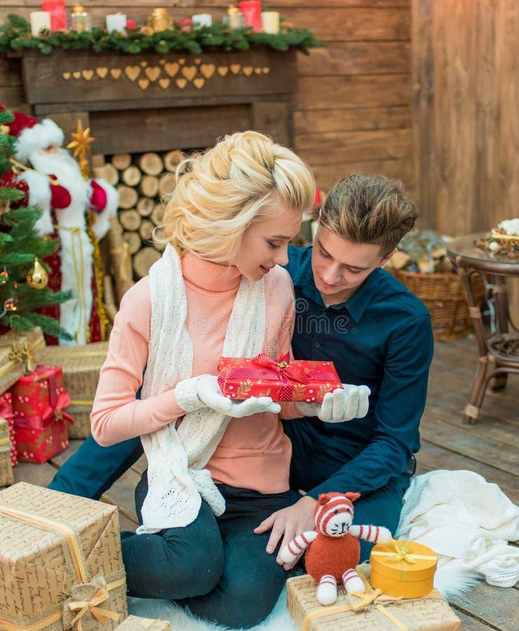 Jeunes couples affectueux de Noël ouvrant un présent ensemble photos stock