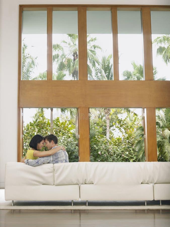Jeunes couples affectueux embrassant sur le sofa photographie stock