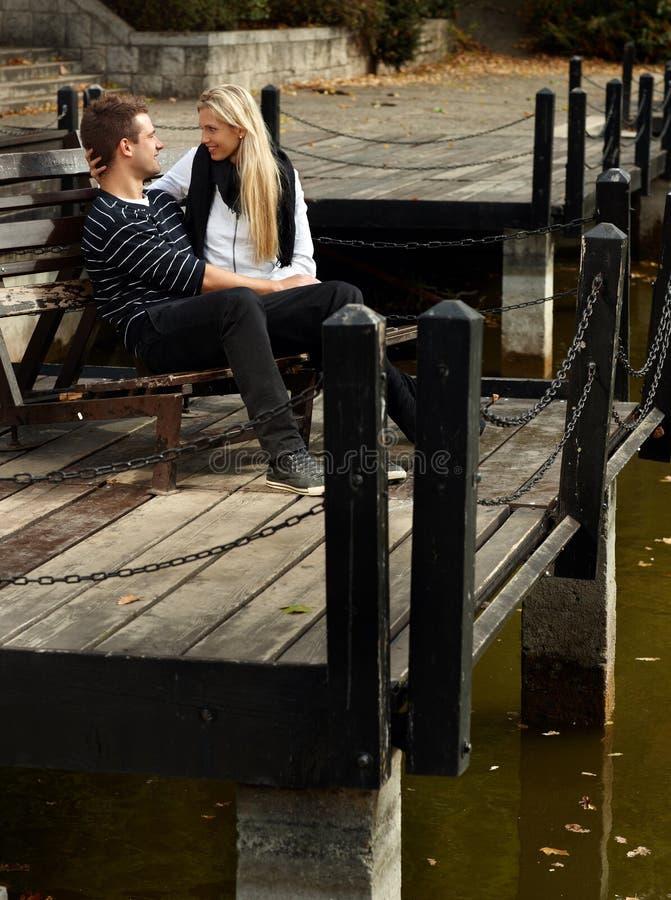 Jeunes couples affectueux en stationnement par le lac photos stock