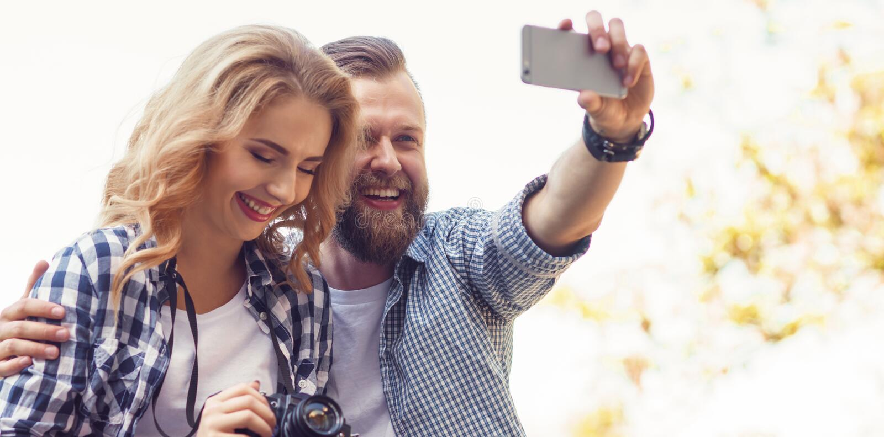 Jeunes couples affectueux faisant la photo de selfie en parc d'automne images stock