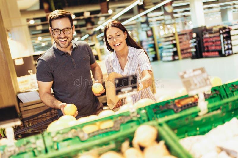 Jeunes couples affectueux gais dans le supermarché avec le chariot de achat choisissant des fruits photographie stock
