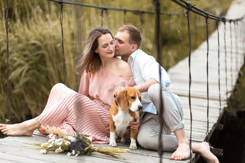 Jeunes couples affectueux heureux étreignant sur le pont au-dessus de la rivière Est tout près leur chien domestique de race de b image libre de droits