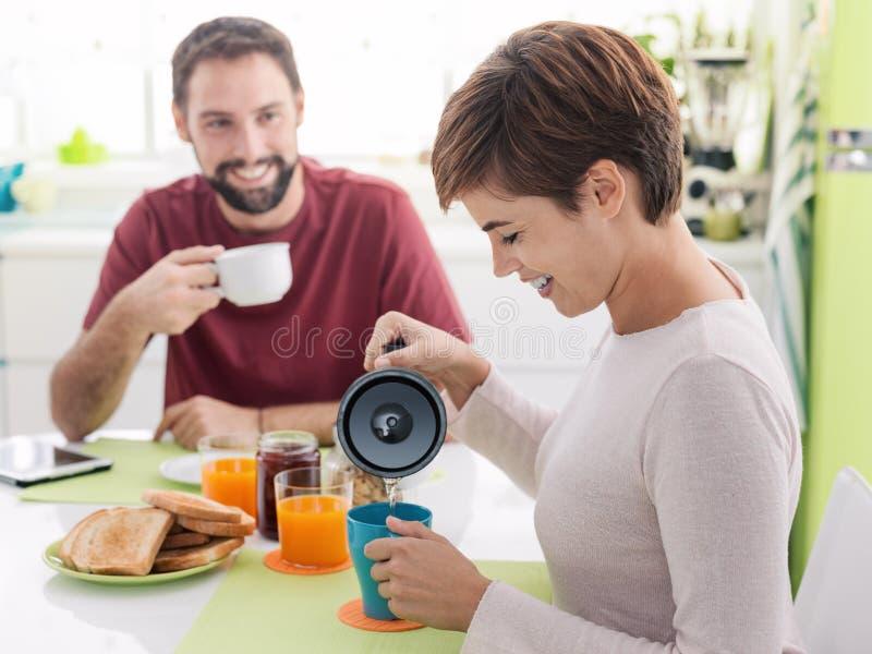 Jeunes couples affectueux prenant le petit déjeuner à la maison images stock