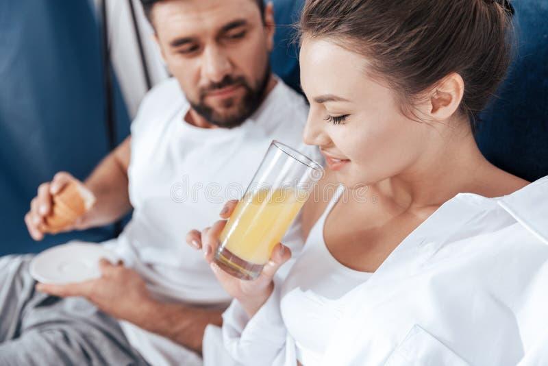 Jeunes couples affectueux prenant le petit déjeuner dans le lit photo libre de droits