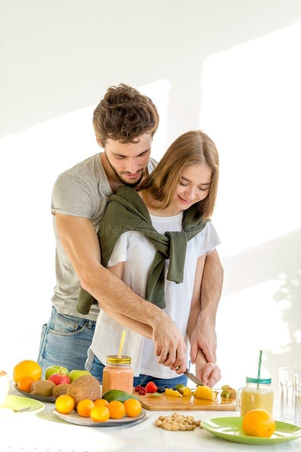 Jeunes couples affectueux romantiques préparant le petit déjeuner photographie stock