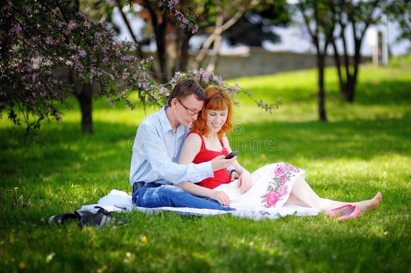 Jeunes couples affectueux se reposant au parc sur l'herbe au printemps photos libres de droits