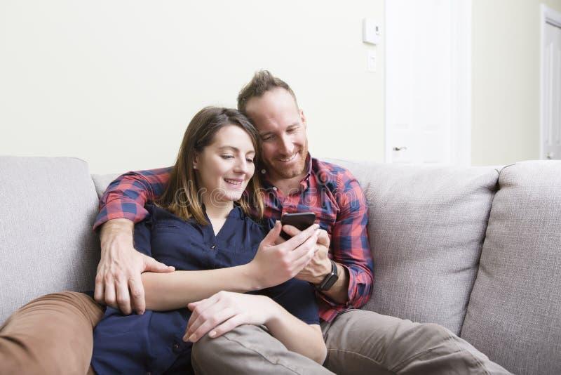 Jeunes couples affectueux se reposant sur le divan à la maison photo stock