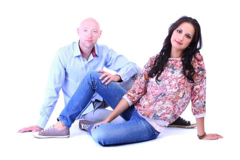 Jeunes couples affectueux se reposant sur le plancher images stock