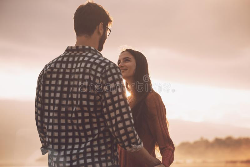 Jeunes couples affectueux tenant des mains au coucher du soleil photos stock