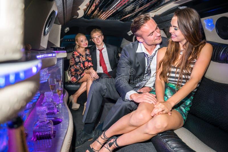 Jeunes couples affectueux voyageant avec des amis dans la limousine photographie stock