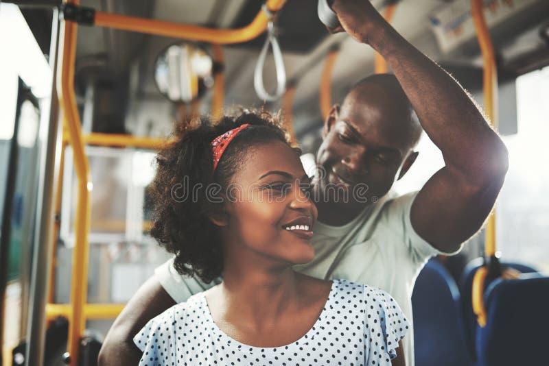 Jeunes couples africains affectueux montant ensemble sur un autobus photos libres de droits