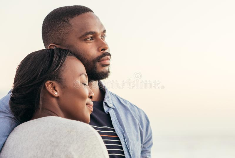 Jeunes couples africains appréciant un coucher du soleil à la plage images stock