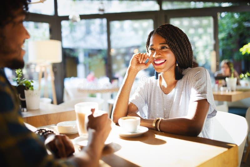 Jeunes couples africains de sourire se reposant à une table à un café potable de café et parlant ensemble photo libre de droits