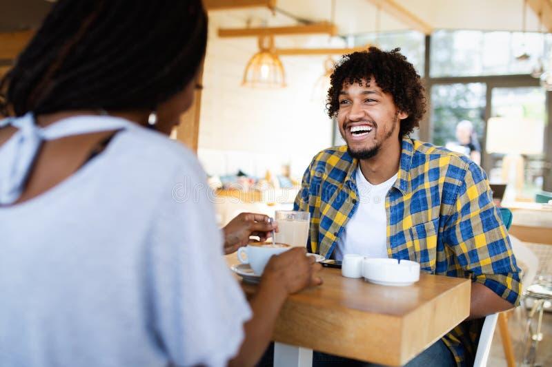 Jeunes couples africains de sourire se reposant ? une table ? un caf? potable de caf? et parlant ensemble image stock