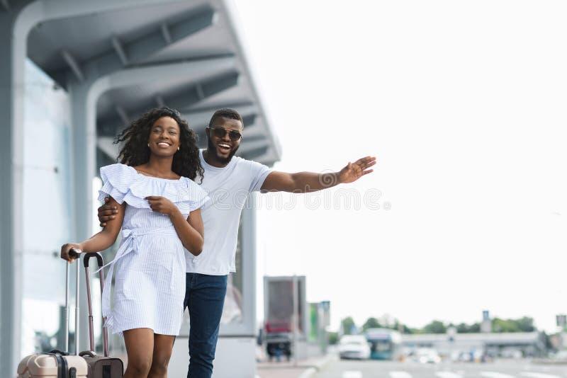 Jeunes couples africains se tenant près de l'aéroport essayant d'arrêter la voiture images libres de droits
