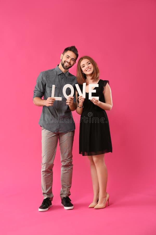 Jeunes couples aimants tenant le mot AMOUR sur le fond de couleur Célébration de Saint-Valentin de saint images stock