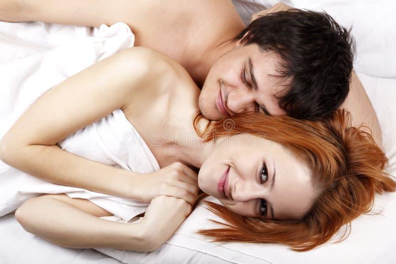 Jeunes couples amoureux heureux attrayants à la chambre à coucher photo stock