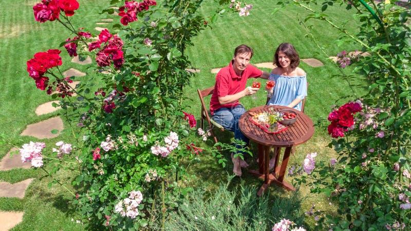 Jeunes couples appréciant la nourriture et le vin dans le beau jardin de roses à la date romantique, à la vue supérieure aérienne images stock