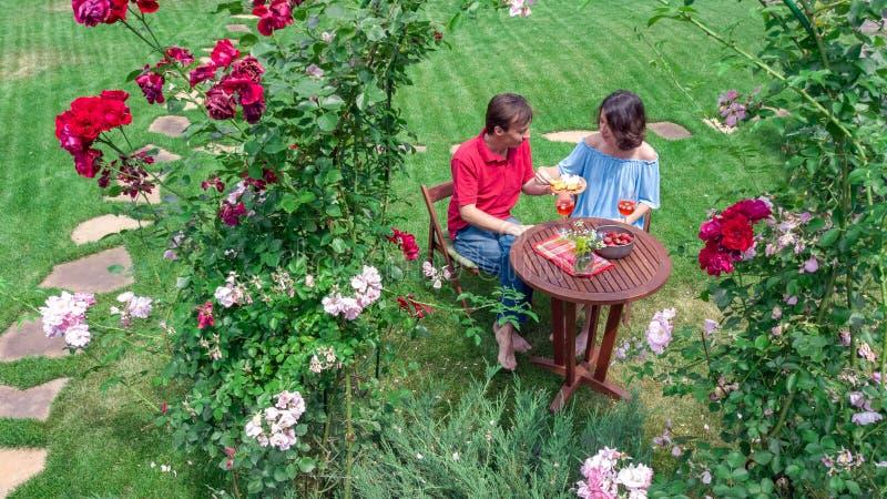 Jeunes couples appréciant la nourriture et le vin dans le beau jardin de roses à la date romantique, à la vue supérieure aérienne photographie stock libre de droits