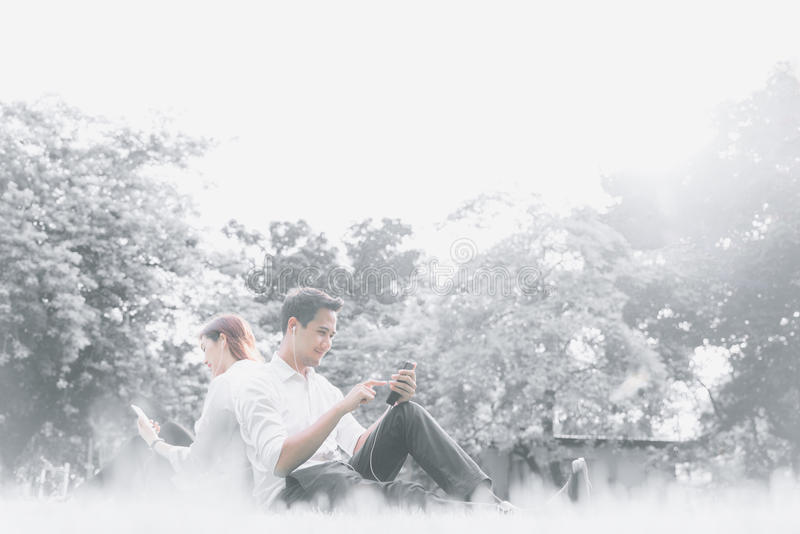 Jeunes couples asiatiques d'étudiant universitaire se reposant et détendant ensemble en parc, écoutant la musique sur des smartph image stock