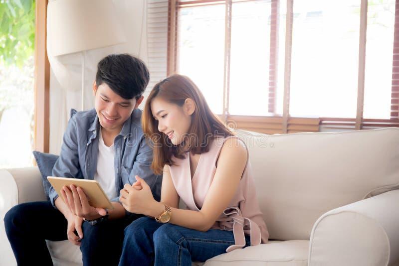 Jeunes couples asiatiques d?tendre regardant le divertissement de comprim? sur l'Internet ensemble sur le sofa ? la maison photo stock