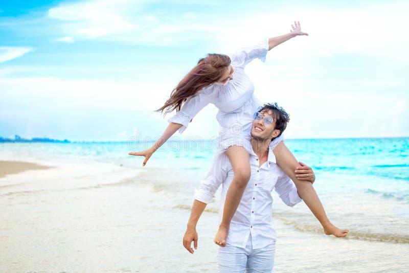 Jeunes couples asiatiques dans la lune de miel d'amour à la plage de mer sur le ciel bleu mari donnant le tour de ferroutage à l' photographie stock libre de droits