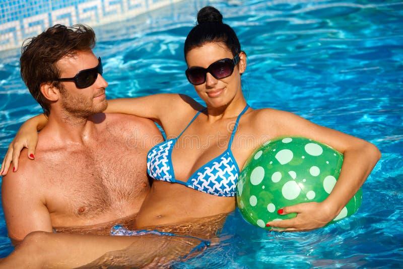 Jeunes couples attrayants dans la piscine images libres de droits