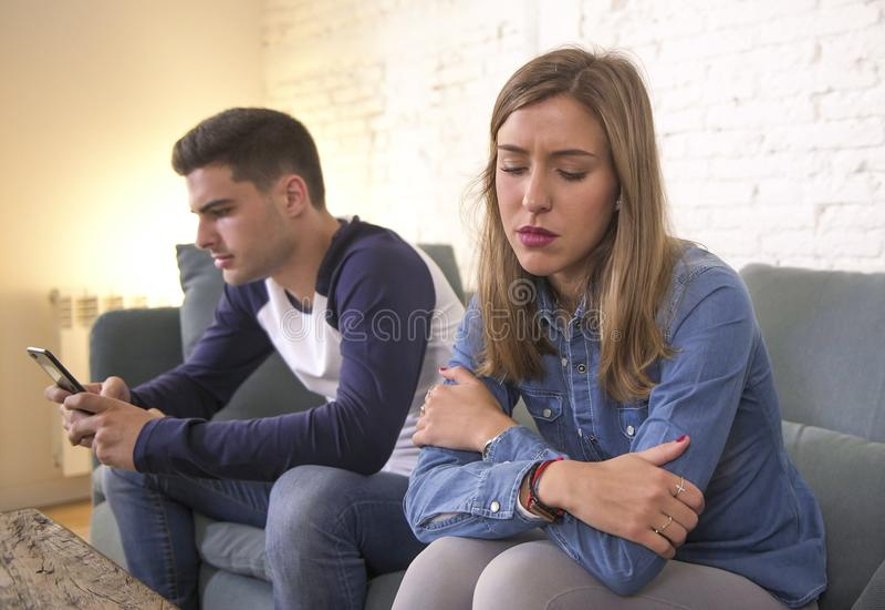 Jeunes couples attrayants dans le problème de relations avec l'ami de dépendance de téléphone portable d'Internet ignorant néglig photo stock
