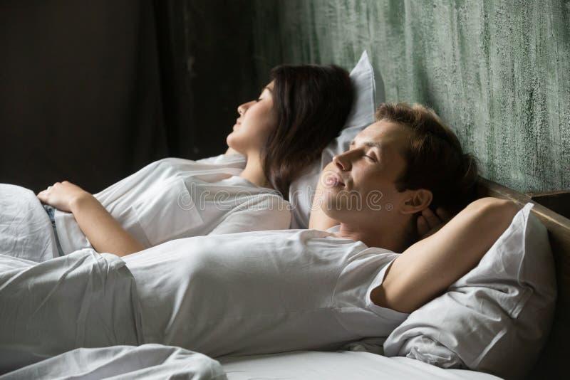 Jeunes couples attrayants dormant dans le lit à la maison photographie stock