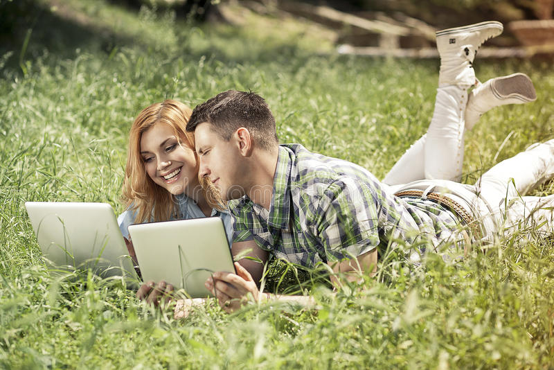 Jeunes couples attrayants se trouvant sur l'herbe, regardant l'ordinateur portable photos libres de droits