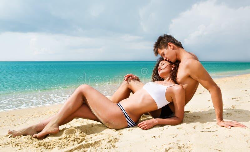 Jeunes couples attrayants sur la plage images stock