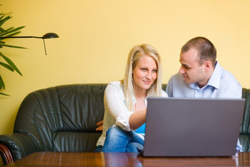 Jeunes couples attrayants utilisant l'ordinateur portatif. photographie stock