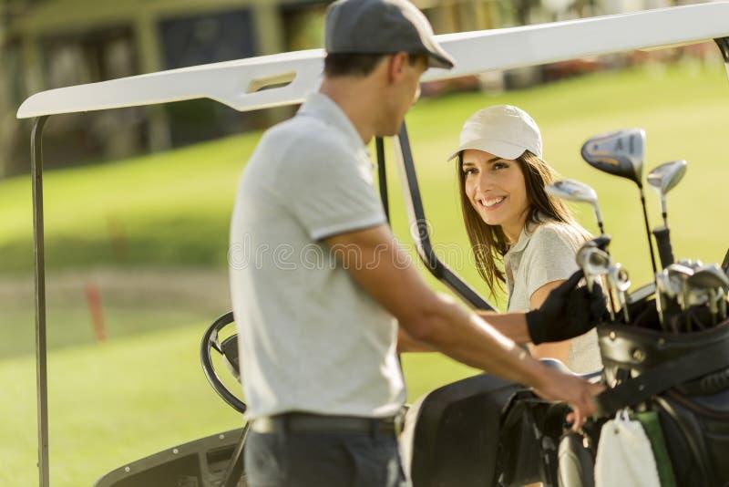 Jeunes couples au chariot de golf images stock