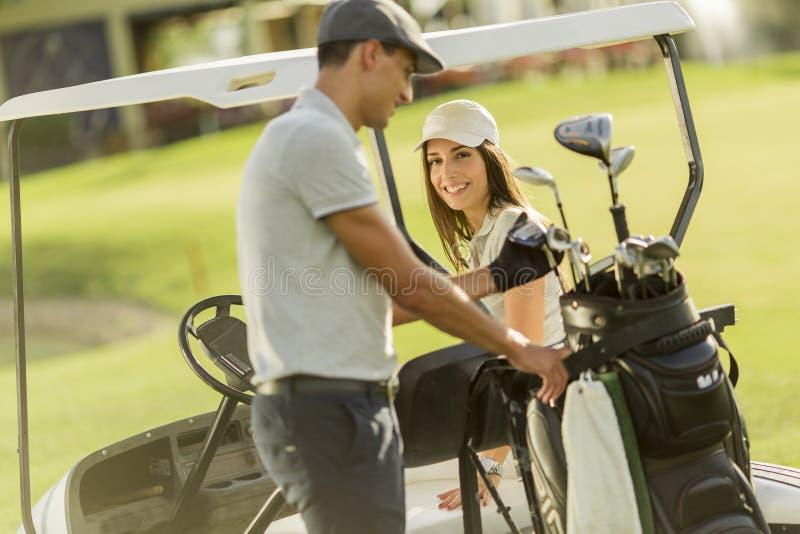 Jeunes couples au chariot de golf photo stock