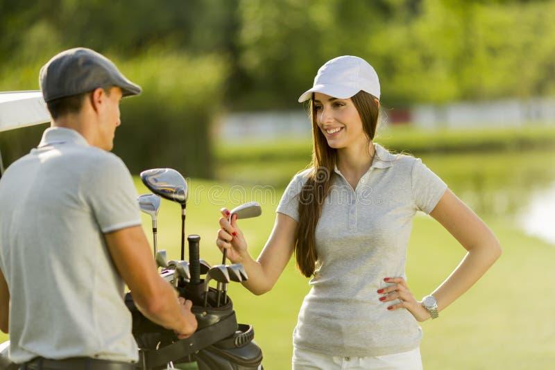 Jeunes couples au chariot de golf images libres de droits