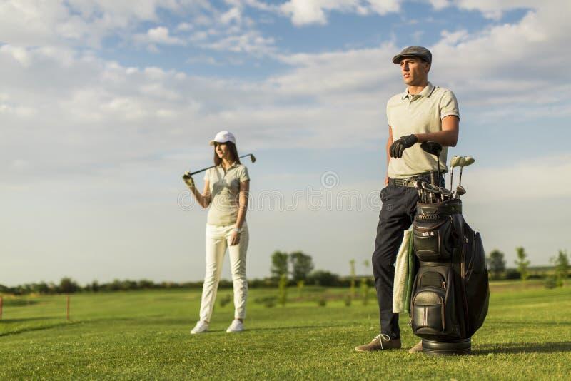 Jeunes couples au chariot de golf photographie stock libre de droits