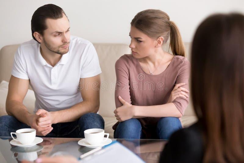 Jeunes couples au psychologue, regardant l'un l'autre avec haine images stock