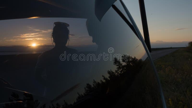 Jeunes couples au tronc d'une voiture au coucher du soleil près de la route image stock