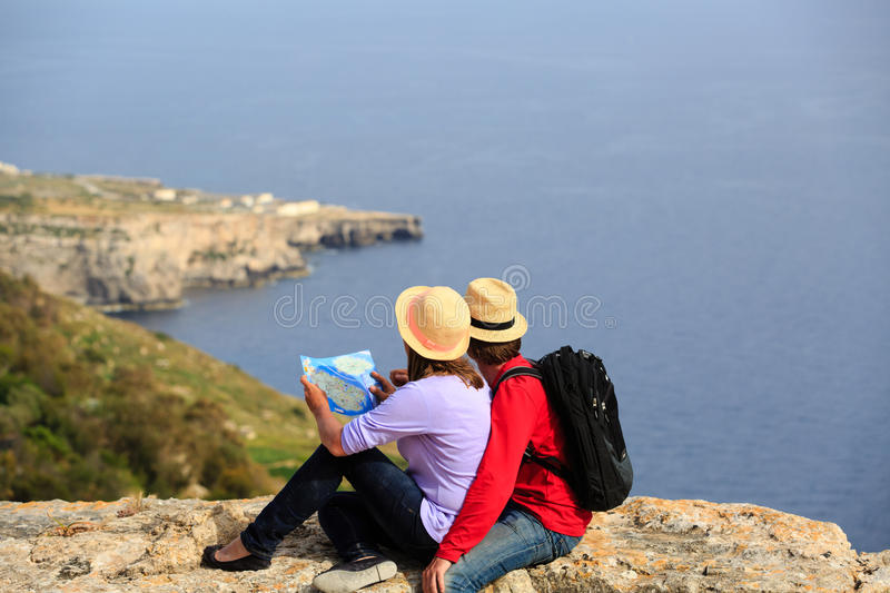 Jeunes couples augmentant en montagnes regardant la carte photo stock
